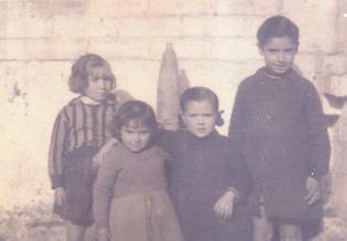 Grup de nenes i nens davant d'un obús o projectil caigut