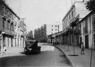 Visió de la carretera Laureà Miró en direcció Barcelona, amb el pas d'un vehicle, a l'alçada dels pisos Bertrand. Any 1927. Fotògraf: Desconegut. ACBL Col·lecció ciutadana d'imatges de Sant Feliu Llobregat.