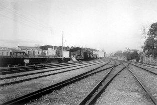 Estació del ferrocarril, amb el moll de descàrrega de mercaderies a l'esquerra i uns vagons situats a les vies mortes. Febrer de 1941. Fotògraf: Pere Gelabert Enrich. ACBL Col·lecció ciutadana d'imatges de Sant Feliu de Llobregat. Imatge cedida per l'autor.